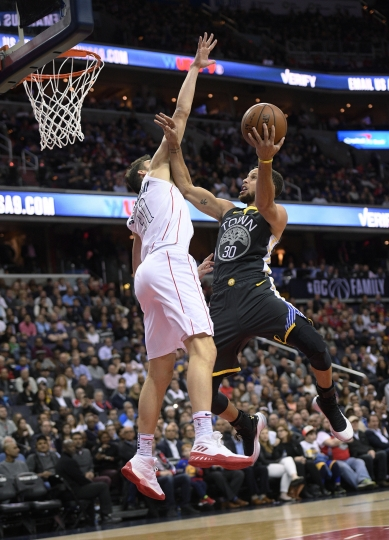 Golden State Warriors guard Stephen Curry (30) goes to the basket against Washington Wizards forward Tomas Satoransky (31), of the Czech Republic, during the first half of an NBA basketball game Wednesday, Feb. 28, 2018, in Washington. (AP Photo/Nick Wass)