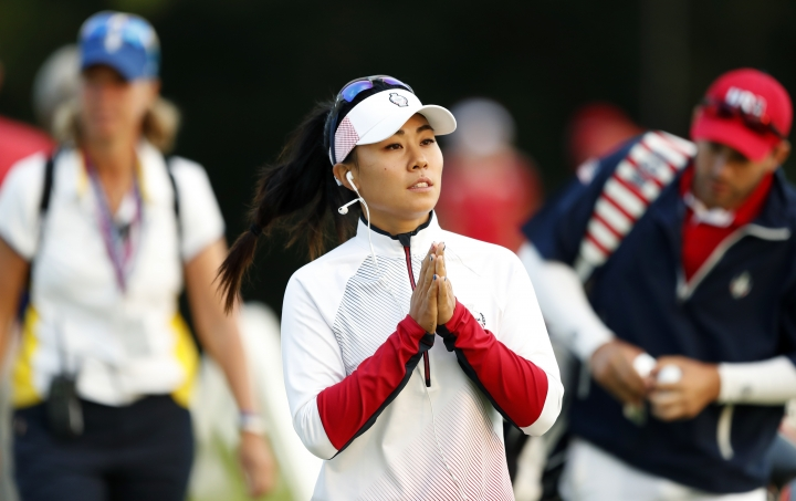 FILE - In this Aug. 18, 2017 file photo, Danielle Kang of the United States, walks to the practice green before her foursome match in the Solheim Cup golf tournament, in West Des Moines, Iowa. Danielle Kang recovered from a bizarre mishap that left her nursing a broken tooth to charge up the leaderboard on the opening day of the LPGA Singapore tournament on Thursday, March 1, 2018. The reigning Women's PGA Championship title holder, Kang said she fell asleep while exercising ahead of her opening round, and woke up feeling pain in her mouth.(AP Photo/Charlie Neibergall, File)