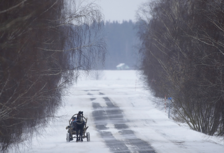 People ride on traditional cart through the snow and wind in the village of Podberezhie, 50 km (31 miles) southeast of Minsk, Belarus, Wednesday, Feb. 28, 2018. Daily temperatures dropped to -13 C ( -8,6 F) in Belarus. (AP Photo/Sergei Grits)