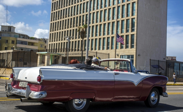 "In this Oct. 3, 2017 photo, tourists ride a classic convertible car on the Malecon beside the United States Embassy in Havana, Cuba. The United States said Friday it was making permanent its decision last year to withdraw 60 percent of its diplomats from Cuba, citing the need to protect American personnel from what the State Department called ""health attacks"" that remain unexplained. (AP Photo/Desmond Boylan)"