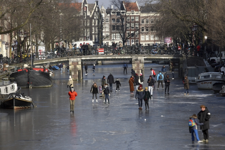 People walk and skate on the frozen Prinsengracht canal in downtown Amsterdam, Friday, March 2, 2018. The icy weather gripping much of Europe is good news for the Dutch, many of whom love to skate on frozen waterways if the weather allows. (AP Photo/Mike Corder)