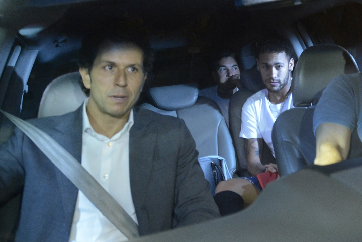 Brazil soccer star Neymar, right, and his doctor Rodrigo Lasmar, left, arrive to the Mater Dei Hospital, in Belo Horizonte, Brazil, Friday, March 2, 2018. Neymar will have surgery on a fractured toe in his right foot and could be out for up to three months, an estimate that would take the Brazil striker right up to the World Cup. Neymar was injured Sunday in Paris Saint-Germain's match against Marseille in the French league. (AP Photo/Eugenio Savio)
