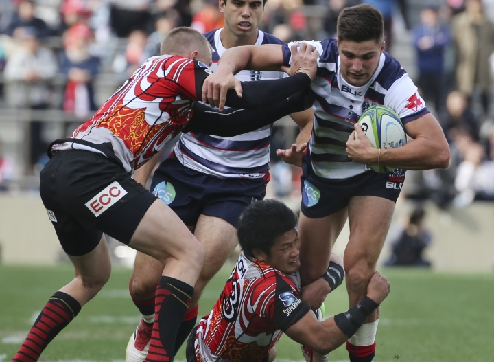 Jack Maddocks of Australia's Rebels, right, is tackled by Ryuji Noguchi, bottom, and Robbie Robinson of Japan's Sunwolves during their Super Rugby match in Tokyo, Saturday, March 3, 2018. (AP Photo/Koji Sasahara)