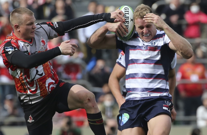 Reece Hodge of Australia's Rebels, right, and Robbie Robinson of Japan's Sunwolves battle for the ball during their Super Rugby match in Tokyo, Saturday, March 3, 2018. (AP Photo/Koji Sasahara)