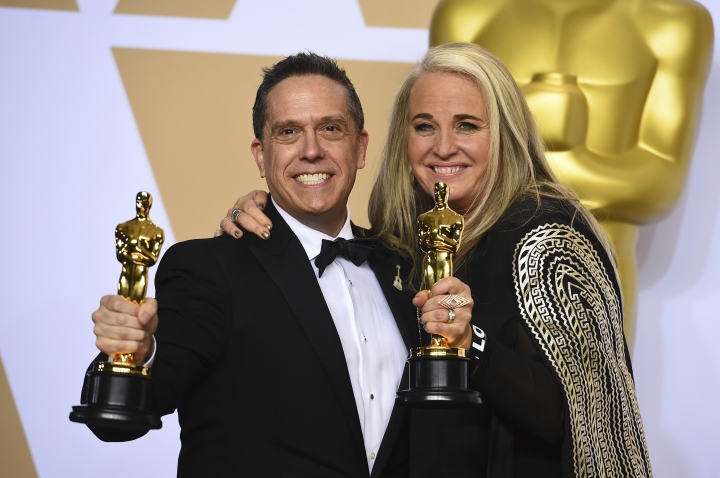 """Lee Unkrich, left, and Darla K. Anderson, winners of the award for best animated feature film for """"Coco"""", pose in the press room at the Oscars on Sunday, March 4, 2018, at the Dolby Theatre in Los Angeles. (Photo by Jordan Strauss/Invision/AP)"""