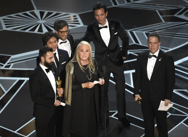 """Darla K. Anderson, center, and from back left, Adrian Molina, Anthony Gonzalez, Gael Garcia Bernal, Benjamin Bratt, and Lee Unkrich accept the award for best animated feature film for """"Coco"""" at the Oscars on Sunday, March 4, 2018, at the Dolby Theatre in Los Angeles. (Photo by Chris Pizzello/Invision/AP)"""