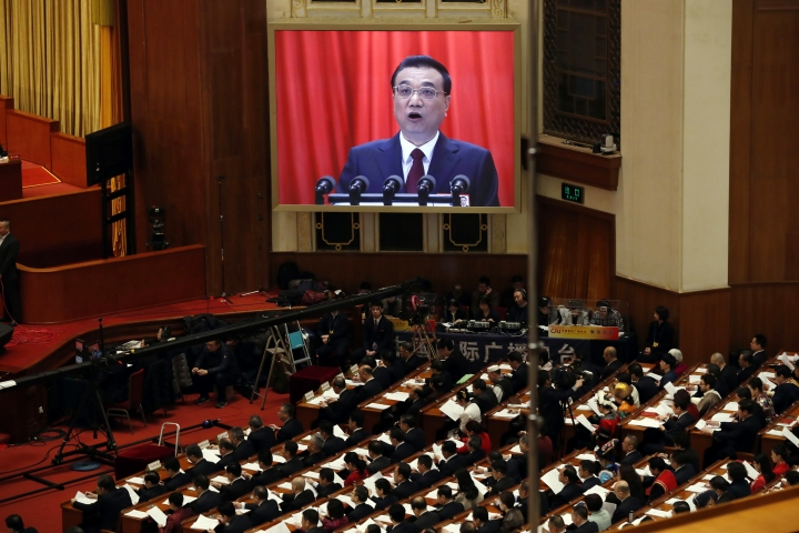 Chinese Premier Li Keqiang is shown on a large screen as he delivers a work report at the opening session of the annual National People's Congress in Beijing's Great Hall of the People, Monday, March 5, 2018. (AP Photo/Ng Han Guan)