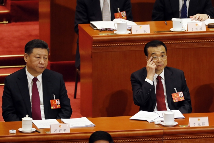 Chinese Premier Li Keqiang, right, gestures near Chinese President Xi Jinping during the opening session of the annual National People's Congress in Beijing's Great Hall of the People, Monday, March 5, 2018. (AP Photo/Ng Han Guan)