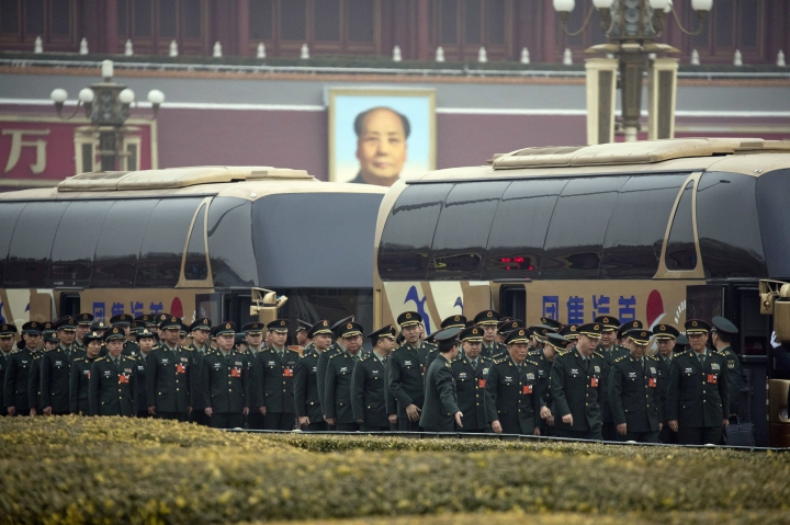 Military delegates arrive on buses near Tiananmen Gate with a giant portrait of Mao Zedong outside the Great Hall of the People on the eve of the annual legislature's opening session in Beijing, Sunday, March 4, 2018. The spokesman for China's ceremonial legislature says Sunday his country has no desire to overturn the existing international order and its increasingly powerful military is no threat to others. (AP Photo/Ng Han Guan)