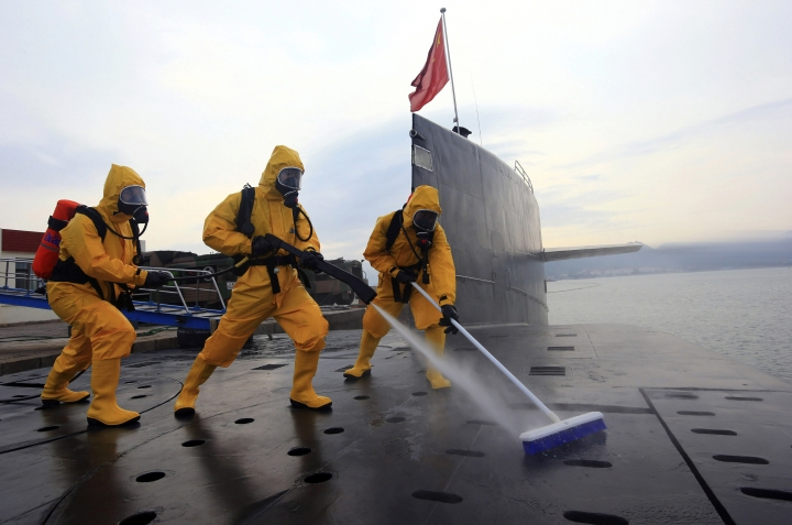 FILE - In this July 17, 2013 file photo released by the Chinese Navy, sailors in protective gears clean and disinfect a nuclear submarine during a drill at the Qingdao submarine base in east China's Shandong province. China's defense budget will rise 8 percent to 1.1 trillion yuan ($173 billion) this year as the country is preparing to launch its second aircraft carrier, integrating stealth fighters into its air force and fielding an array of advanced missiles able to attack air and sea targets at vast distances, according to a report released Monday, March 5, 2018. (Color China Photo via AP Photo, File)