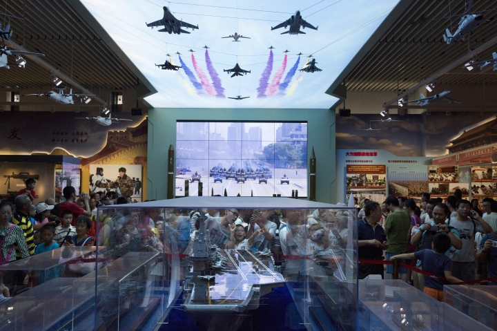 FILE - In this Aug. 1, 2017, file photo, visitors look at a scale model of a Chinese aircraft carrier during an exhibition to mark the 90th anniversary of the founding of the People's Liberation Army at the military museum in Beijing. China's defense budget will rise 8 percent to 1.1 trillion yuan ($173 billion) this year as the country is preparing to launch its second aircraft carrier, integrating stealth fighters into its air force and fielding an array of advanced missiles able to attack air and sea targets at vast distances, according to a report released Monday, March 5, 2018. (AP Photo/Ng Han Guan, File)