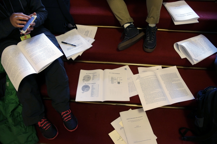 Journalists read the government's work report during the opening session of the annual National People's Congress at the Great Hall of the People in Beijing, Monday, March 5, 2018. (AP Photo/Andy Wong)