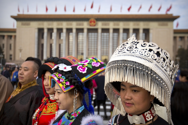 Delegates in ethnic minority dress stand outside the Great Hall of the People before the opening session of China's National People's Congress (NPC) in Beijing, Monday, March 5, 2018. China's government pledged Monday to deliver robust growth, pursue advanced technology and boost military spending while urging the public to embrace President Xi Jinping's rule as its ceremonial legislature prepared for changes to allow him to stay in power indefinitely. (AP Photo/Mark Schiefelbein)