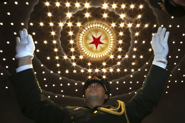 A Chinese military band conductor leads the band at the end of the opening session of the annual National People's Congress in Beijing's Great Hall of the People, Monday, March 5, 2018. China's government pledged Monday to deliver robust growth, pursue advanced technology and boost military spending while urging the public to embrace President Xi Jinping's rule as its ceremonial legislature prepared for changes to allow him to stay in power indefinitely.(AP Photo/Ng Han Guan)