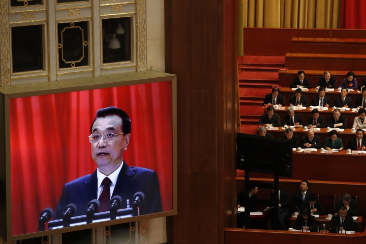 Chinese Premier Li Keqiang is shown on a large screen as he delivers a work report during the opening session of the annual National People's Congress in Beijing's Great Hall of the People, Monday, March 5, 2018. China's government pledged Monday to deliver robust growth, pursue advanced technology and boost military spending while urging the public to embrace President Xi Jinping's rule as its ceremonial legislature prepared for changes to allow him to stay in power indefinitely.(AP Photo/Ng Han Guan)