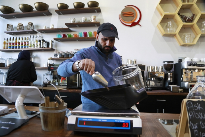 In this Jan. 9, 2018, photo, Ibrahim Alhasbani, owner of Qahwah House, a cafe that serves coffee made from beans harvested on his family's farm in Yemen's mountains, measures coffee beans in Dearborn, Mich. Yemeni have been coming to the U.S. for more than a century _ especially since the 1960s _ but in recent years they have been planting stronger roots, raising their profile and looking outward _ opening upscale restaurants and cafes and running for political office. And, in cases like Alhasbani, they are making Yemeni culture a key part of the business proposition. (AP Photo/Carlos Osorio)