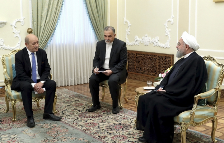 "In this photo released by an official website of the office of the Iranian Presidency, President Hassan Rouhani, right, meets with French Foreign Minister Jean-Yves Le Drian at the start of their meeting, in Tehran, Iran, Monday, March 5, 2018. Le Drian met stiff resistance from his Iranian counterpart, who said Western arms deals had turned the Middle East into a ""gunpowder depot."" His one-day trip Monday highlighted the challenge Paris faces in challenging Iran while at the same time trying to keep the 2015 nuclear deal with world powers intact. (Iranian Presidency Office via AP)"