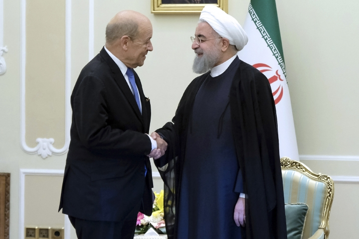 "In this photo released by an official website of the office of the Iranian Presidency, President Hassan Rouhani, right, greets French Foreign Minister Jean-Yves Le Drian at the start of their meeting, in Tehran, Iran, Monday, March 5, 2018. Le Drian met stiff resistance from his Iranian counterpart, who said Western arms deals had turned the Middle East into a ""gunpowder depot."" His one-day trip Monday highlighted the challenge Paris faces in challenging Iran while at the same time trying to keep the 2015 nuclear deal with world powers intact. (Iranian Presidency Office via AP)"