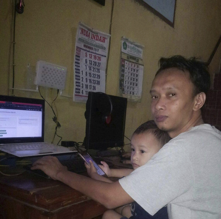 This Wednesday, Nov. 29, 2017, photo provided by Aria Khrisna shows Krishna and his 3-year-old son Raka. Khrisna, a 36-year-old father of three in Tegal, Indonesia, says doing things like adding word tags to clothing pictures on websites such as eBay and Amazon pays him about $100 a month, roughly half his income. (Indah Nurul Hidayah/Aria Khrisna via AP)