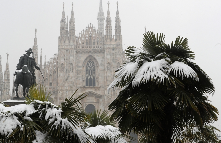 FILE - In this March 2, 2018, file photo, palm trees are dusted in snow after a snowfall in front of Milan's Gothic Cathedral, Italy. New U.S. weather data shows that the Arctic just finished its warmest winter on record, with plenty of open water where the ocean normally freezes. The National Snow and Ice Data Center said Tuesday, March 6, the extent of Arctic sea ice in February was 62,000 square miles (160,000 square kilometers) smaller than last year's record low. (AP Photo/Antonio Calanni, File)