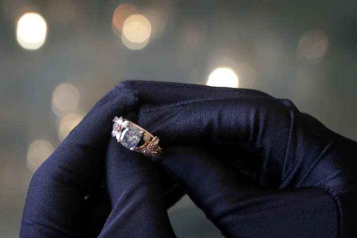 CORRECTS DETAILS OF THE CAPTION In this Sunday, March 4, 2018, photo, Karan Tilani, director of the World of Diamonds Group, holds the 2.08-carat Jane Seymour blue diamond ring which his company designed and owns. A $2 million initial coin offering backed by the ring that gave investors a chance at a raffle for a luxury dinner was called off on Tuesday, March 6 2018. The event's organizer, V Diamonds, said it would process thousands of refunds for investors who bought tokens for an ownership stake in the ring(AP Photo/Wong Maye-E)