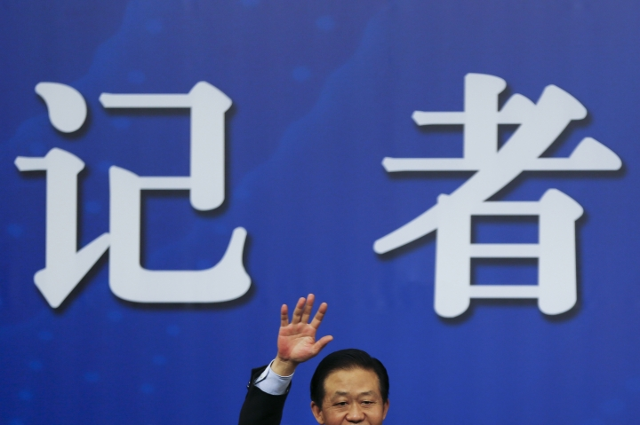 China's Finance Minister Xiao Jie waves as he arrives for a press conference on the sidelines of the National People's Congress at the media center in Beijing, Wednesday, March 7, 2018. Xiao tried Wednesday to defuse concern over the country's rising debt, saying government borrowing is below danger levels and regulators can prevent financial system risks. (AP Photo/Andy Wong)