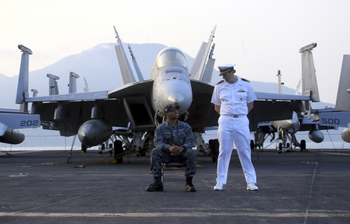 American navy officers talk to each other aboard the aircraft carrier USS Carl Vinson as it docks in Danang bay, Vietnam on Monday, March 5, 2018. For the first time since the Vietnam War, a U.S. Navy aircraft carrier is paying a visit to a Vietnamese port, seeking to bolster both countries' efforts to stem expansionism by China in the South China Sea. (AP Photo/ Hau Dinh)