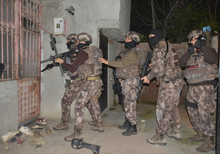 Turkey's special police officers prepare to storm a house during an operation to arrest Islamic State group suspects, in the southern city of Adana, Turkey, early Wednesday, March 7, 2018. Turkey's state-run news agency says police in simultaneous dawn raids at homes, have detained 13 Islamic State group suspects who were allegedly plotting attacks on a number of buildings in the city, including the U.S. Consulate. (Gokhan Keskinci/DHA-Depo Photos via AP)