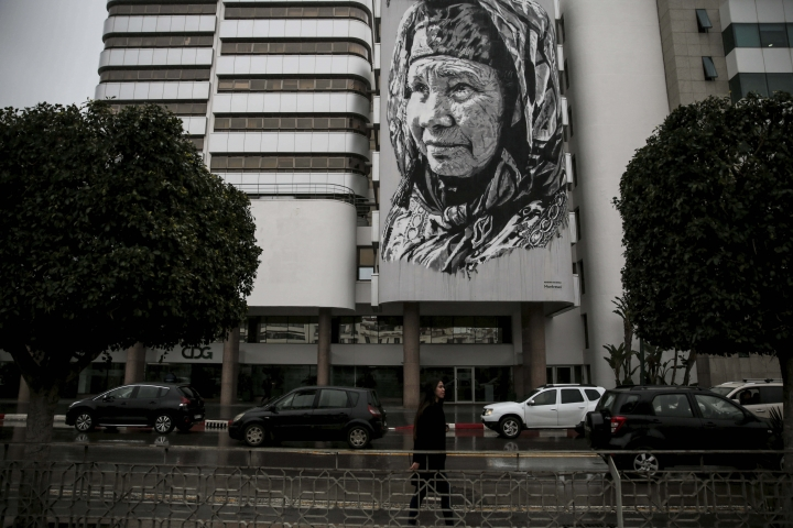 In this Wednesday, March 7, 2018 photo, cars drive past a large mural by German artist Hendrik Beikirch depicting a Moroccan woman, in Rabat, Morocco. Morocco's Parliament passed a long-sought law last month on combating violence against women. It recognizes some forms of abuse for the first time and criminalizes some forms of domestic violence. But critics say it doesn't go nearly far enough to address the deep-seated problem.(AP Photo/Mosa'ab Elshamy)