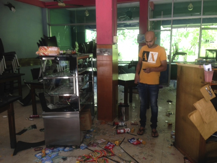 Mohamed Ramzeen makes a call from his mobile phone standing in his vandalized small restaurant in Pilimathalawa, Sri Lanka, Thursday, March 8, 2018. About 50 people broke into Ramzeen's small restaurant on Wednesday night while the curfew was in effect, destroying nearly everything they found, he said. Buddhist mobs swept through Muslim neighborhoods in Sri Lanka's central hills, destroying stores and restaurants despite a curfew, a state of emergency and a heavy deployment of security forces. (AP Photo/ Bharatha Mallawarachchi)