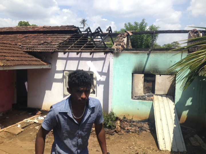 A Sri Lankan walks past a burnt house in Pallekele, Sri Lanka, Thursday, March 8, 2018. Residents say Buddhist mobs have swept through Muslim neighborhoods in Sri Lanka's central hills, destroying stores and restaurants despite a curfew, a state of emergency and a heavy deployment of security forces. (AP Photo/Bharatha Mallawarachchi)