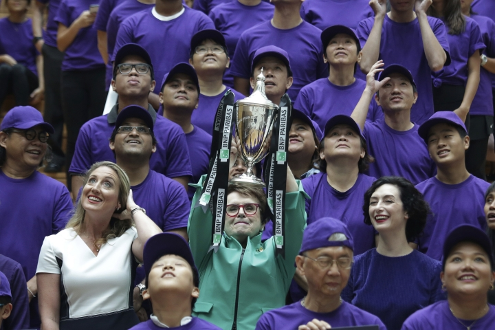 Billie Jean King, founder of the Women's Tennis Association (WTA) and former World No. 1 professional tennis player lifts the WTA challenge trophy named after her, at an event organized by WTA to launch the last edition of the WTA Finals in Singapore, before it moves to Shenzhen in 2019, as well as to commemorate International Women's Day on Thursday, March 8, 2018, in Singapore. (AP Photo/Wong Maye-E)