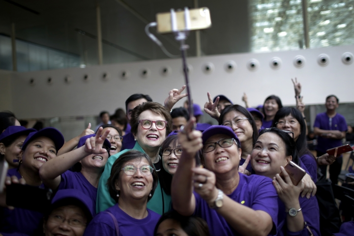 Billie Jean King, founder of the Women's Tennis Association (WTA) and former World No. 1 professional tennis player poses with fans for a selfie during an event organized by the WTA to launch the last edition of the WTA Finals in Singapore, before it moves to Shenzhen in 2019, as well as to commemorate International Women's Day on Thursday, March 8, 2018, in Singapore. (AP Photo/Wong Maye-E)