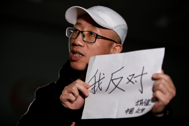"Chinese activist Hu Jia holds a paper as he speaks during an interview with Reuters in Beijing, China February 28, 2018. Picture taken February 28, 2018. The Chinese characters read, ""I object"". REUTERS/Thomas Peter"