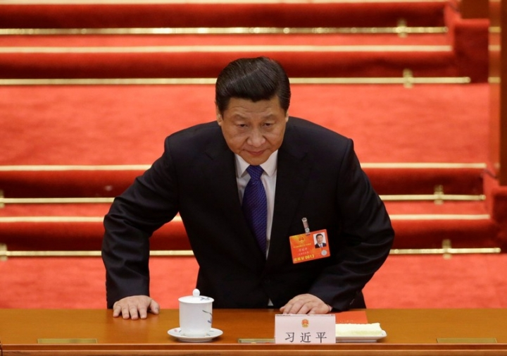 FILE PHOTO: China's newly elected President Xi Jinping takes a seat before the fifth plenary meeting of the National People's Congress (NPC) at the Great Hall of the People in Beijing, March 15, 2013. REUTERS/Jason Lee/File Photo