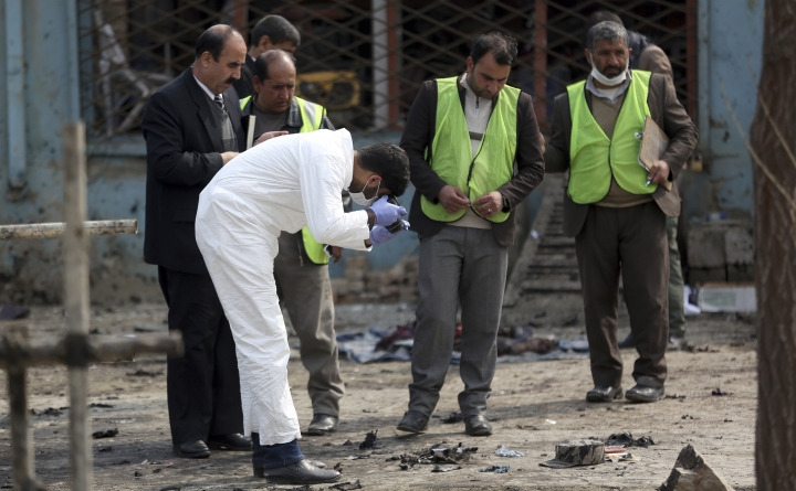 Security personnel inspect the site of a suicide attack in Kabul, Friday, March 9, 2018. A suicide bomber targeting Afghanistan's minority Hazaras blew himself up at a police checkpoint in western Kabul on Friday, killing nine people and wounding more than a dozen, officials said. (AP Photo/Massoud Hossaini)