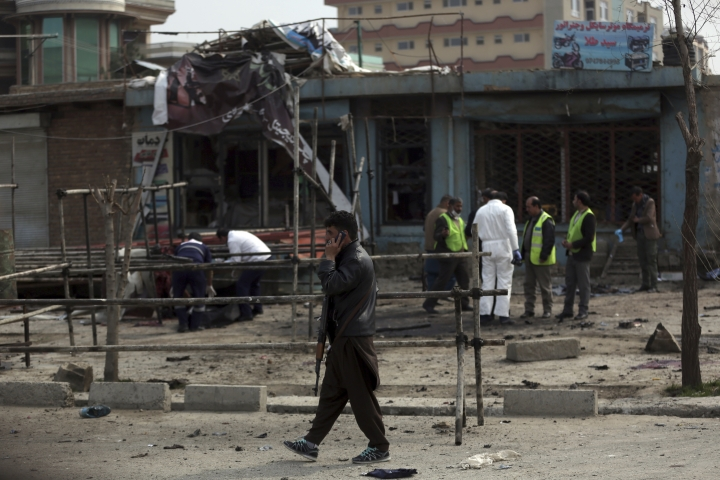 A security officer talks on the phone at the site of a suicide attack in Kabul, Friday, March 9, 2018. A suicide bomber targeting Afghanistan's minority Hazaras blew himself up at a police checkpoint in western Kabul on Friday, killing nine people and wounding more than a dozen, officials said. (AP Photo/Massoud Hossaini)