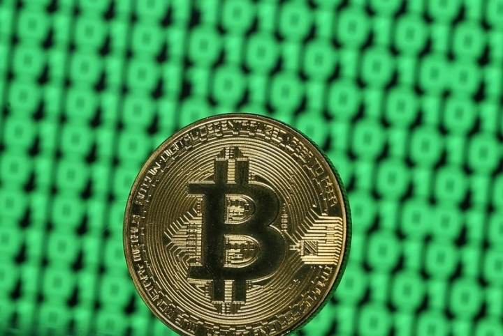 FILE PHOTO: A token of the virtual currency Bitcoin is seen placed on a monitor that displays binary digits in this illustration picture, December 8, 2017. REUTERS/Dado Ruvic/Illustration