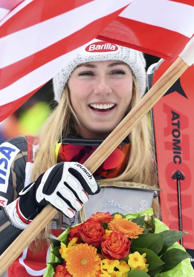 United States' Mikaela Shiffrin waves a US flag after winning an alpine ski, women's World Cup slalom, in Ofterschwang, Germany, Saturday, March 10, 2018. (AP Photo/Marco Tacca)