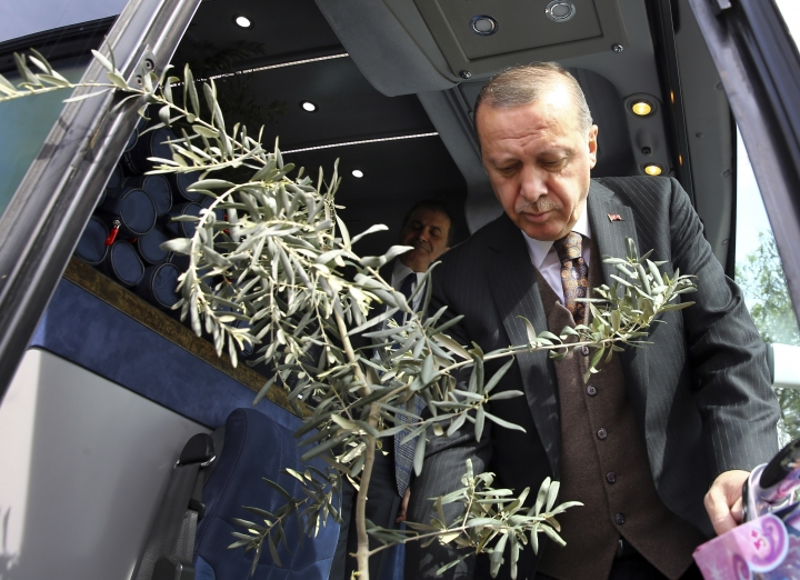 """Turkey's President Recep Tayyip Erdogan, holding an olive branch arrives to deliver a speech at a rally of his ruling Justice and Development (AKP) Party's supporters, in Mersin, southern Turkey, Saturday, March 10, 2018. Erdogan has criticised NATO for not supporting the country's ongoing military operation against the Syrian Kurdish People's Protection Units or YPG, named 'Olive Branch', that started Jan. 20, to clear them from Afrin in northwestern Syria. Erdogan asked, """"Hey NATO, where are you?"""" and accused the alliance of double standards. (Pool Photo via AP)"""