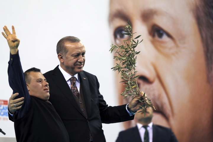 "Turkey's President Recep Tayyip Erdogan, holding an olive branch, embraces a supporter after delivering a speech at a rally of his ruling Justice and Development (AKP) Party's supporters, in Mersin, southern Turkey, Saturday, March 10, 2018. Erdogan has criticised NATO for not supporting the country's ongoing military operation against the Syrian Kurdish People's Protection Units or YPG, named 'Olive Branch', that started Jan. 20, to clear them from Afrin in northwestern Syria. Erdogan asked, ""Hey NATO, where are you?"" and accused the alliance of double standards. (Pool Photo via AP)"