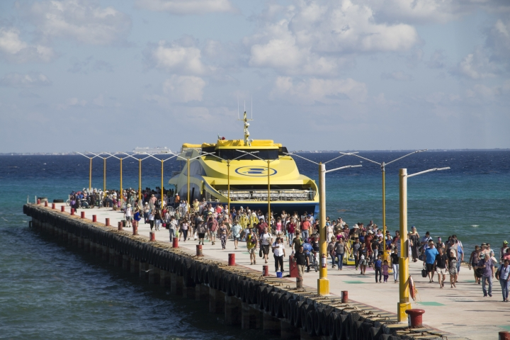 "In this Friday, March 2, 2018 photo, tourists and passengers disembark from a ferry on to the wharf on Playa del Carmen, Mexico. In a notice posted Friday, March 9, on its website, the U.S. Embassy in Mexico has narrowed its travel warning for the Caribbean resort city of Playa del Carmen amid what it calls an unspecified ""ongoing security threat"" just as the spring holiday season is kicking into high gear. (AP Photo/Gabriel Alcocer)"