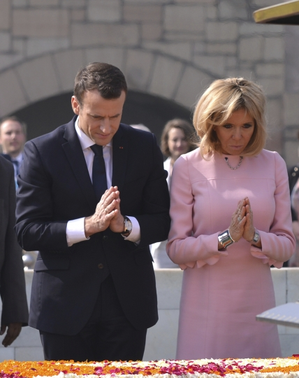 French President Emmanuel Macron, left, and wife Brigitte, offer tributes at Rajghat, Mahatma Gandhi memorial, in New Delhi, India, Saturday, March 10, 2018. Macron who is on a four-day state visit is expected to hold talks with Indian Prime Minister Narendra Modi and co-chair the Founding Conference of the International Solar Alliance. (AP Photo)