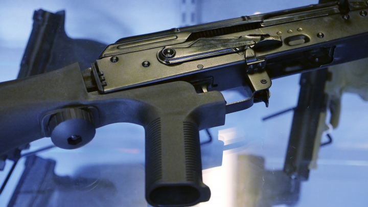 "FILE - In this Oct. 4, 2017 file photo, a device called a ""bump stock"" is attached to a semi-automatic rifle at the Gun Vault store and shooting range in South Jordan, Utah. The Trump administration is proposing banning bump stocks, which allow guns to mimic fully automatic fire and were used in last year's Las Vegas massacre. The Justice Department's regulation, announced Saturday, March 10, 2018, would classify the device as a machine gun prohibited under federal law. The move was expected after President Donald Trump ordered officials to work toward a ban after 17 people were killed at a Florida high school. (AP Photo/Rick Bowmer, File)"