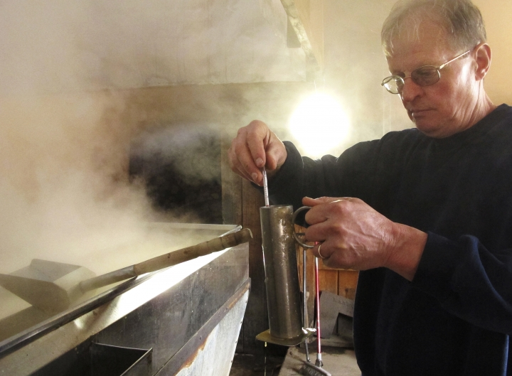 In this March 7, 2018, photo, Doug Bragg of Bragg Farm Sugarhouse & Gift Shop in East Montpelier, Vt., tests the density, or sugar content, of maple syrup being boiled from sap. Maple syrup season started early this year in parts of New England. The head of the maple syrup makers association in Vermont said some producers have been producing a fair amount of syrup since mid-February. Historically the season has started later. (AP Photo/Lisa Rathke)