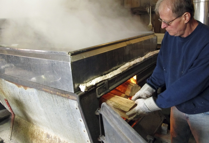 In this March 7, 2018, photo, Doug Bragg of Bragg Farm Sugarhouse & Gift Shop in East Montpelier, Vt., loads firewood into an evaporator that fuels the boiling of maple sap into syrup. Maple syrup season started early this year in parts of New England. The head of the maple syrup makers association in Vermont said some producers have been producing a fair amount of syrup since mid-February. Historically the season has started later. (AP Photo/Lisa Rathke)