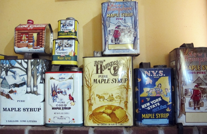 In this March 7, 2018, photo, old maple syrup cans are displayed at Bragg Family Sugarhouse & Gift Shop in East Montpelier, Vt. Maple syrup season started early this year in parts of New England. The head of the maple syrup makers association in Vermont said some producers have been producing a fair amount of syrup since mid-February. Historically the season has started later. (AP Photo/Lisa Rathke)