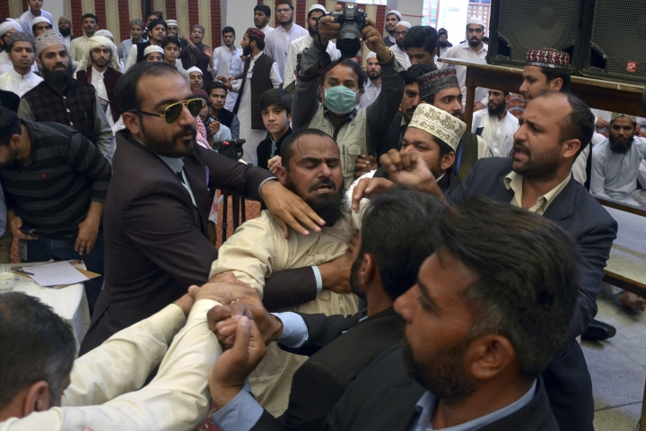 A man is taken away by Pakistani security officials after he hurled a shoe at former Prime Minister Nawaz Sharif during a ceremony in the eastern city of Lahore Pakistan, Sunday, March 11, 2018. Pakistani police said they arrested the man and his accomplice for throwing a shoe at Sharif. (AP Photo/Hamza Ahmed)