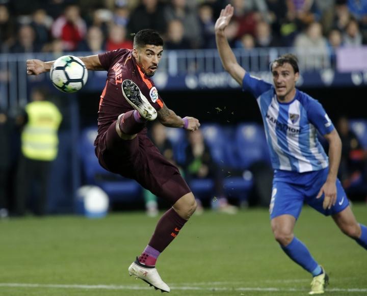 Barcelona's Suarez fights for the ball against Malaga's Ignasi Miquel during a Spanish La Liga soccer match between Malaga and Barcelona in Malaga, Spain, Saturday, March 10, 2018. (AP Photo/M.Pozo)