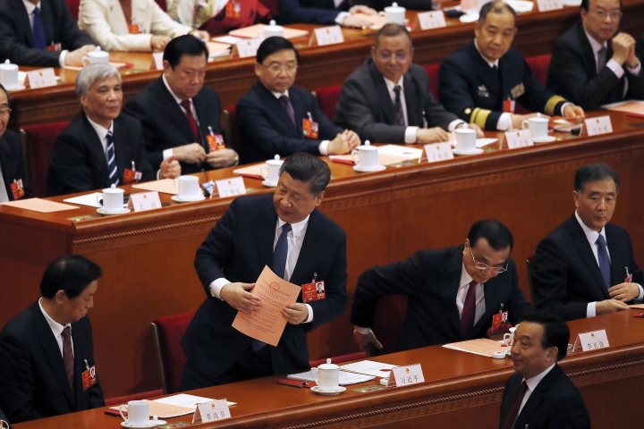 Chinese President Xi Jinping, front row second from left, and Premier Li Keqiang, second from right, proceed to cast their votes for an amendment to China's constitution that will abolish term limits on the presidency and enable Xi to rule indefinitely, during a plenary session of the National People's Congress at the Great Hall of the People in Beijing, Sunday, March 11, 2018. (AP Photo/Andy Wong)